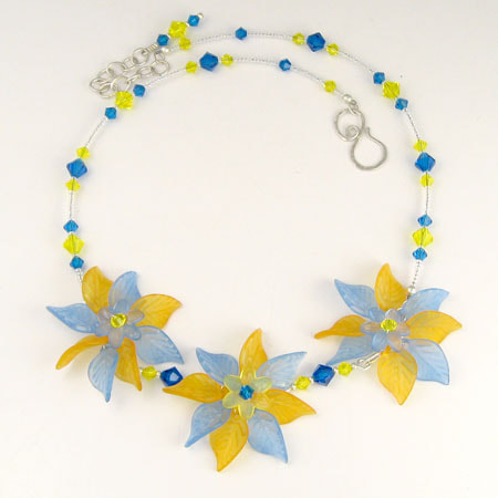 Three flowers composed of translucent Lucite flower and leaf beads in blue and yellow form the center of this necklace. Links of Preciosa crystal beads in Capri blue and citrine connect the flowers and form the back of the necklace. The necklace is adjustable from approximately 17-1/2 inches to 19-1/2 inches. The sterling silver S hook clasp is hand-forged.