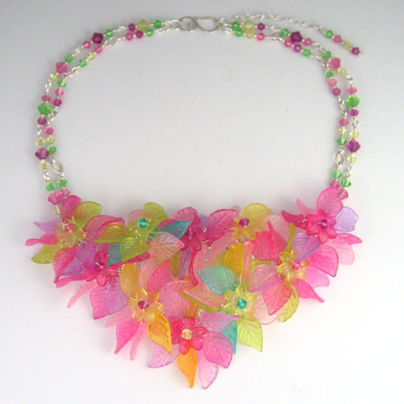 A centerpiece of Lucite flowers and leaves in spring greens, pinks and yellow hangs from a chain made of crystal bead links. Closes with a hand-forged sterling S-hook.