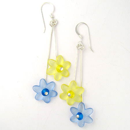 Two translucent Lucite flowers, one yellow and the other blue, with sparkling Preciosa crystal centers drop from sterling silver ear wires. The yellow flower is slightly shorter than the blue flower. The earrings are approximately 1-3/4 inches long from the bottom of the ear wire.