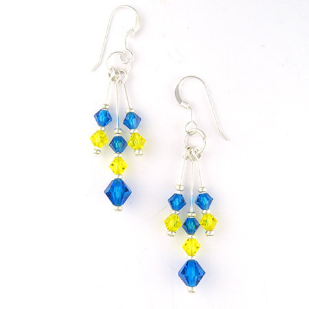 Three columns of Preciosa crystals in yellow and blue zircon dangle from sterling silver ear wires. The middle dangle is slightly longer than the other two and ends with a slightly larger crystal. The earrings are about 1-3/8 inches long from the bottom of the ear wire.